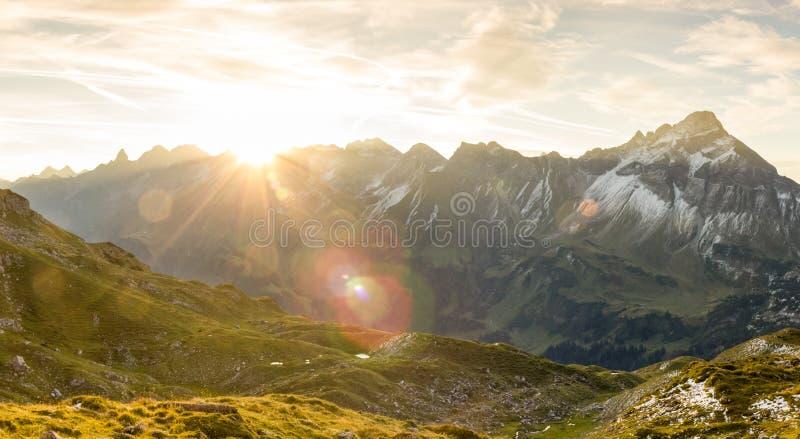 Salida del sol asombrosa en las montañas Llamaradas y rayos de sol agradables de la lente imagen de archivo