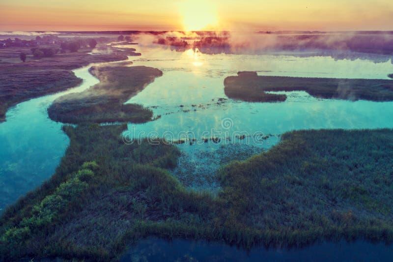 Salida del sol brumosa mágica sobre el río Silueta del hombre de negocios Cowering foto de archivo