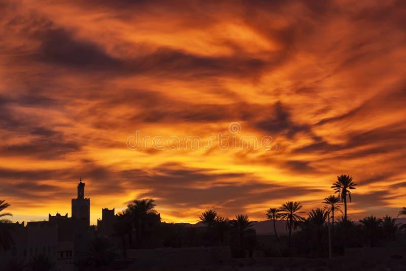 Salida del sol colorida con la mezquita y las palmas datileras. imagen de archivo