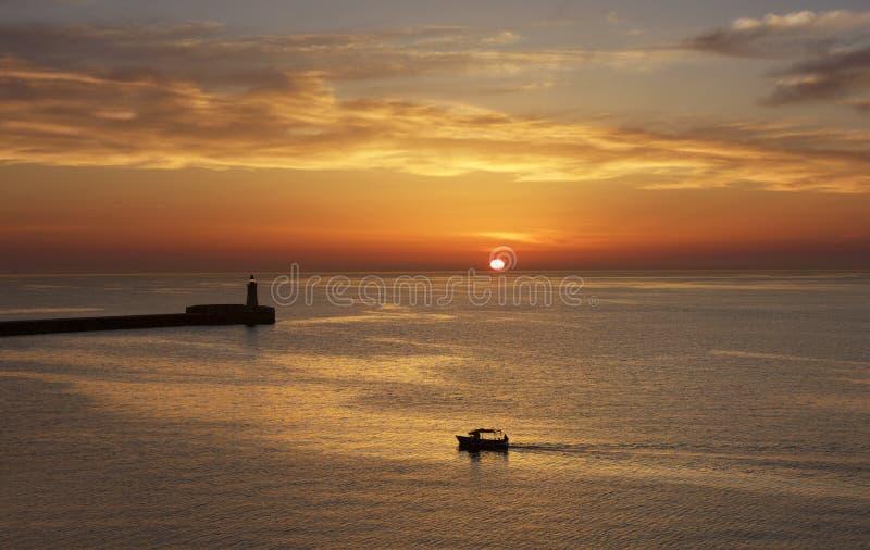 Salida del sol colorida en La Valeta, Malta con el faro y el barco de pesca en el fondo fotografía de archivo libre de regalías