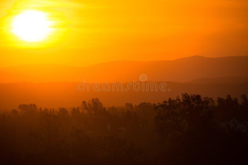 Salida del sol colorida nebulosa de la montaña en Redding California, con los colores de la naranja, rojos y amarillos imagen de archivo libre de regalías