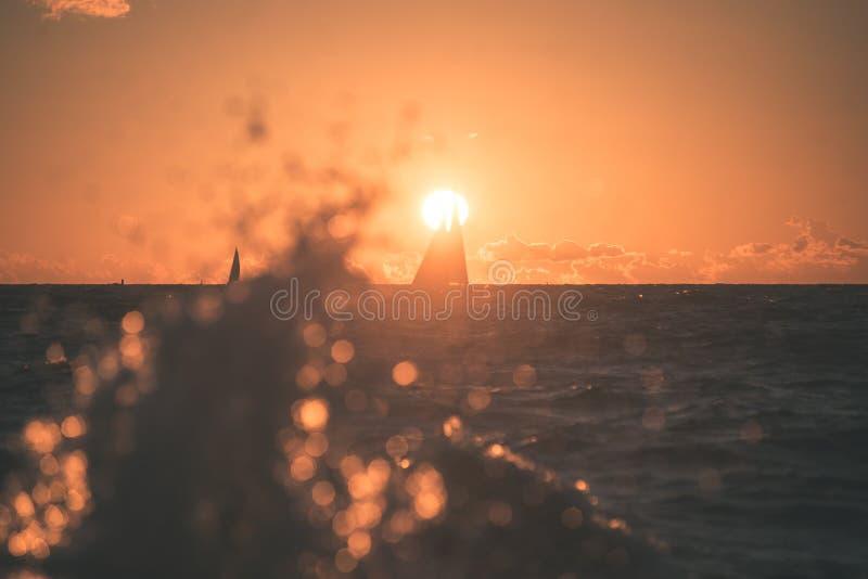 salida del sol colorida sobre el lago con el bote pequeño - efecto del vintage fotos de archivo