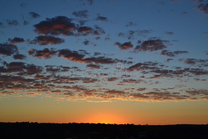 Salida del sol con el cielo de las nubes, anaranjado y azul imagen de archivo libre de regalías