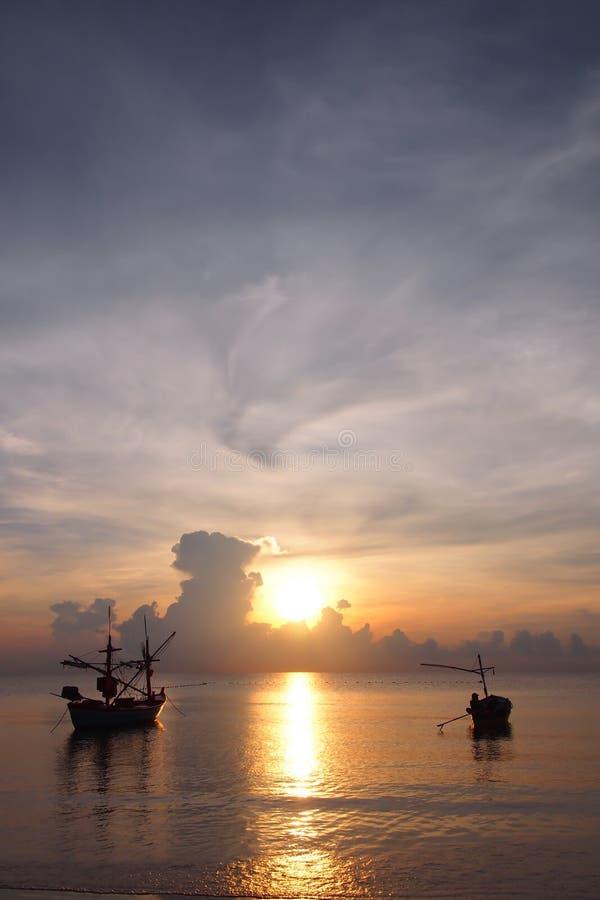 Salida del sol con los pescadores que preparan el barco para salir pescar imagenes de archivo