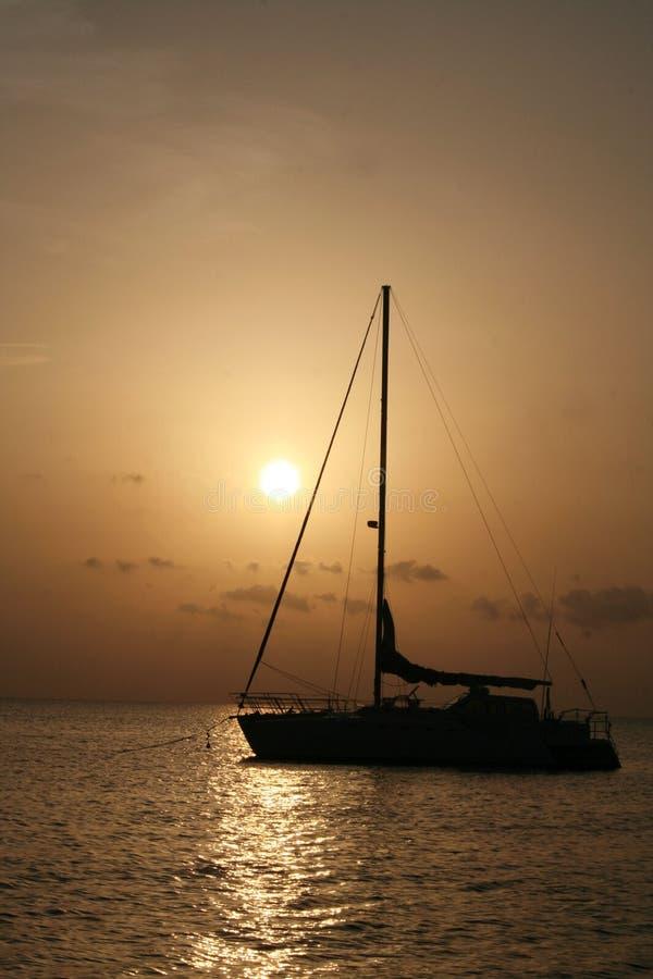 Salida del sol de la silueta del velero imagenes de archivo