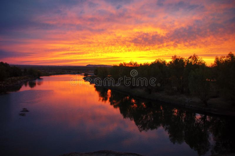 Salida del sol de oro con las nubes llameantes coloridas, la luz roja de la reflexi?n del r?o como puesta del sol imagenes de archivo