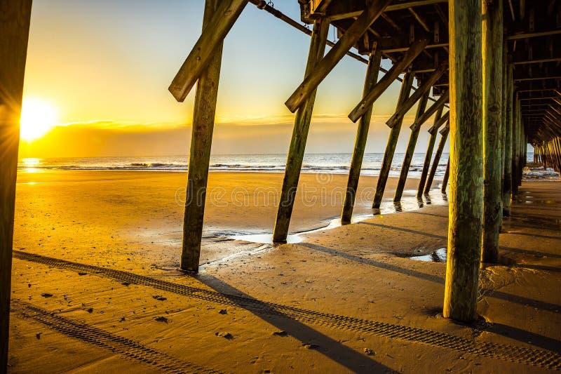 Salida del sol debajo de Myrtle Beach Fishing Pier fotografía de archivo libre de regalías