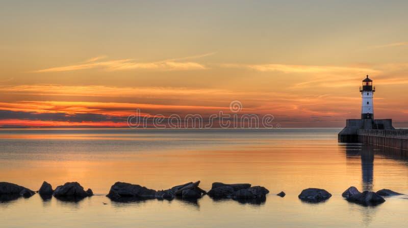 Salida del sol del faro del gran lago con las rocas fotografía de archivo libre de regalías