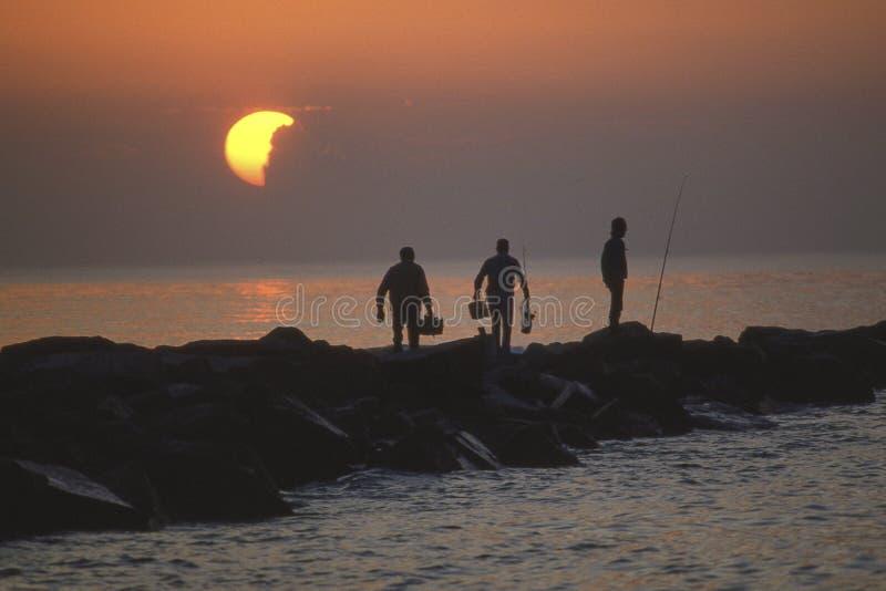 Salida del sol del océano de las siluetas de los pescadores fotos de archivo libres de regalías