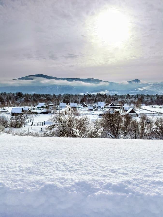 Salida del sol dramática del invierno sobre el pueblo en las montañas de Altai, Kazajistán Nevado imágenes de archivo libres de regalías