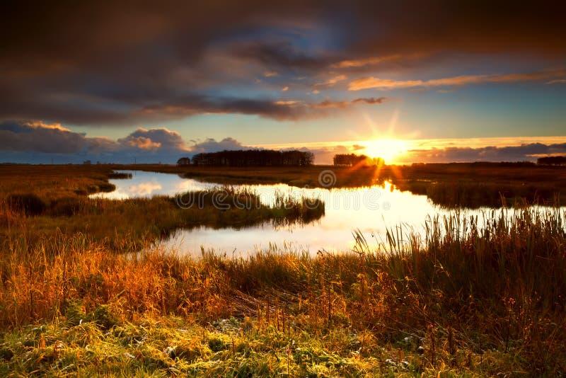 Salida del sol dramática sobre el lago imagenes de archivo