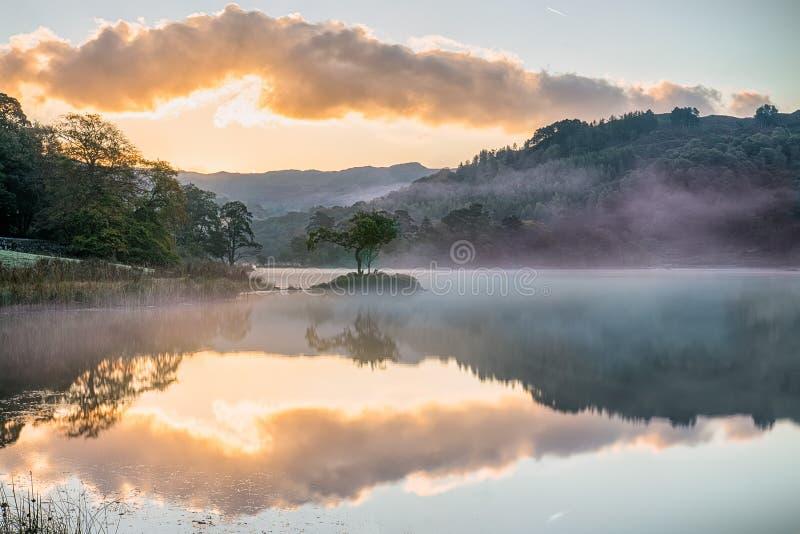Salida del sol duplicada en el agua de Rydal, en el distrito del lago imagenes de archivo