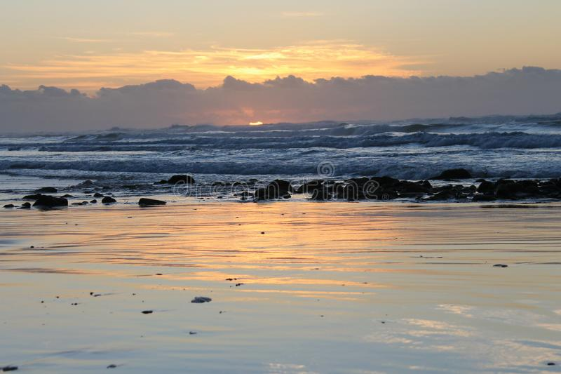 Salida del sol durante la bajamar en la bahía Londres del este de Morgan en la costa salvaje de Suráfrica fotografía de archivo
