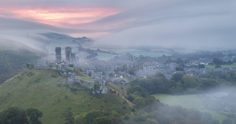 Salida del sol en el castillo de Corfe en niebla foto de archivo