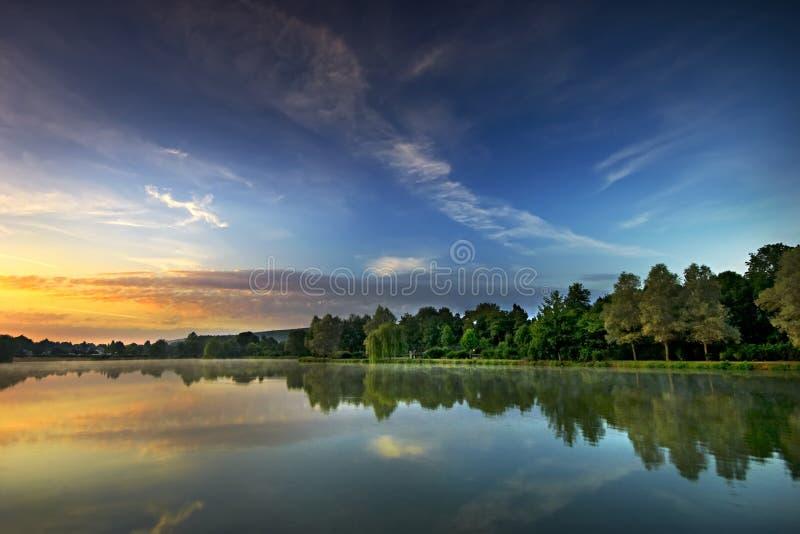 Salida del sol en el lago imagen de archivo