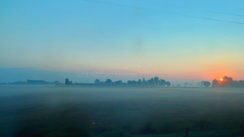 Salida del sol en el llano con niebla imágenes de archivo libres de regalías