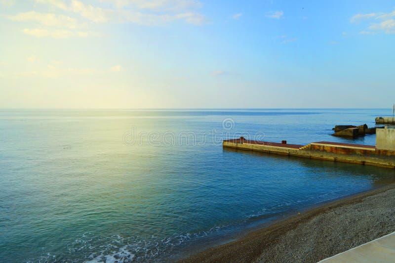 Salida del sol en el mar con resplandor del sol, embarcadero en la orilla en la madrugada, calma, resto, concepto de las vacacion fotografía de archivo libre de regalías