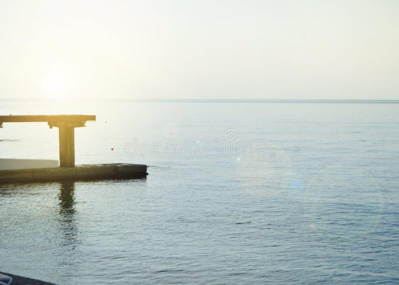 Salida del sol en el mar con resplandor del sol, embarcadero en la orilla en la madrugada, calma, resto, concepto de las vacacion fotografía de archivo