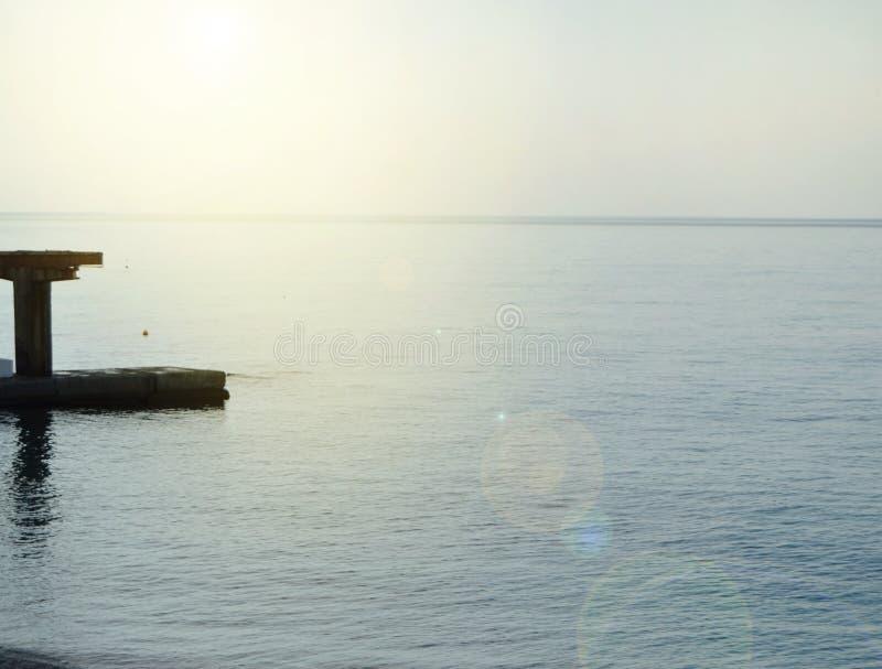 Salida del sol en el mar con resplandor del sol, embarcadero en la orilla en la madrugada, calma, resto, concepto de las vacacion fotos de archivo
