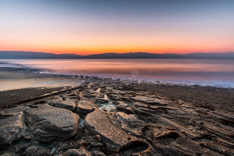 Salida del sol en el mar muerto, rocas grandes en la playa, Israel foto de archivo libre de regalías