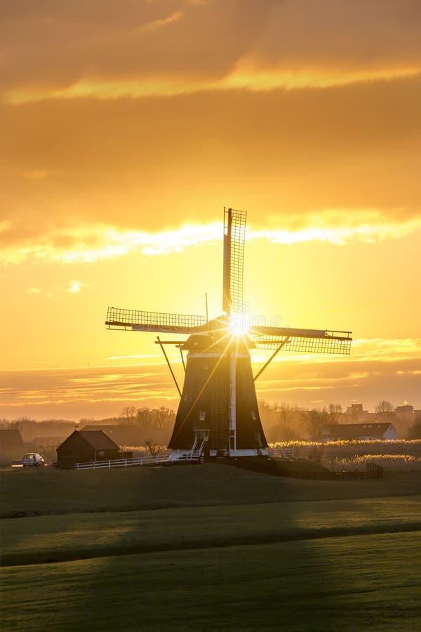 Salida del sol en el molino de viento holandés imagenes de archivo