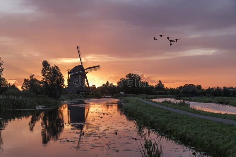 Salida del sol en el molino de viento holandés fotos de archivo