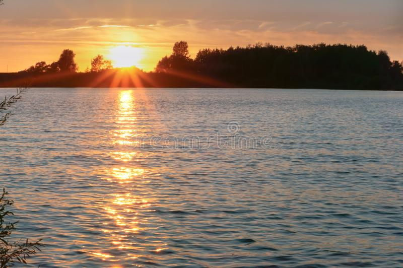 Salida del sol en el río, la reflexión de los rayos del sol en la charca imagenes de archivo