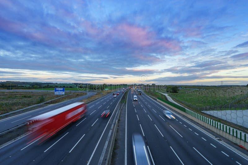 Salida del sol en la autopista M1 con los coches en el movimiento foto de archivo libre de regalías