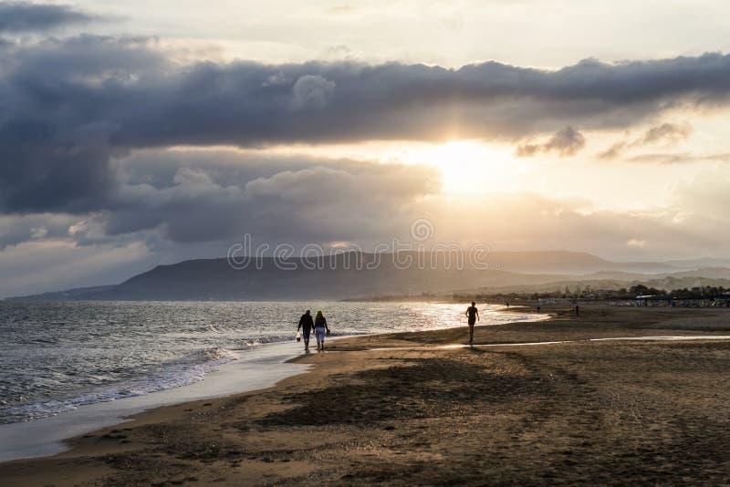 Salida del sol en la playa con el mar y la gente que camina fotos de archivo libres de regalías