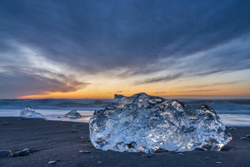 Salida del sol en la playa del diamante, cerca de la laguna del glaciar de Jokulsarlon, con un bloque de hielo grande foto de archivo