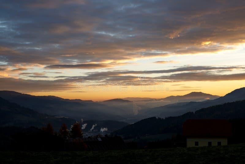 Salida del sol en las montañas austríacas que brillan en las nubes místicas encima de un valle el dormir en Estiria en las montañ imagen de archivo libre de regalías