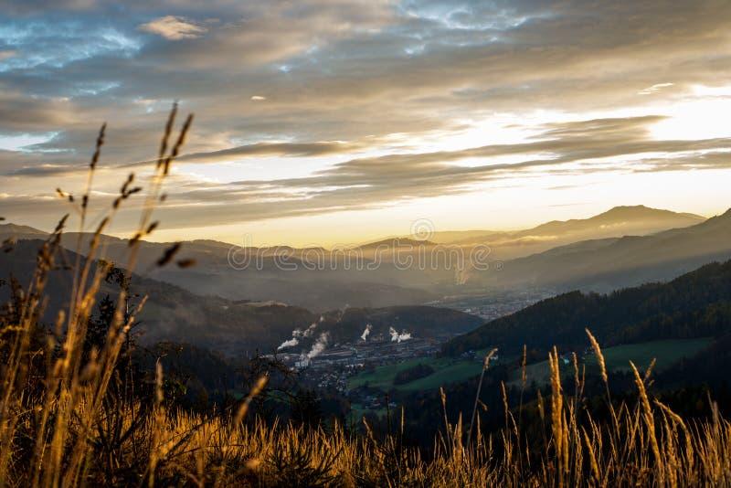Salida del sol en las montañas austríacas que brillan en un valle el dormir y nubes místicas en Estiria fotos de archivo libres de regalías