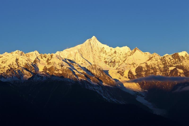 Salida del sol en las montañas de la nieve imagenes de archivo