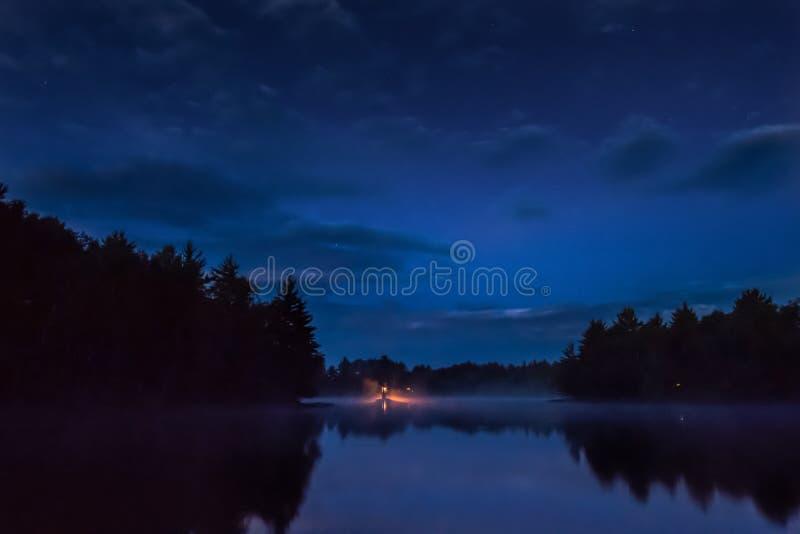 Salida del sol en luz roja del pequeño lago de la locura en el banco lejano fotos de archivo libres de regalías