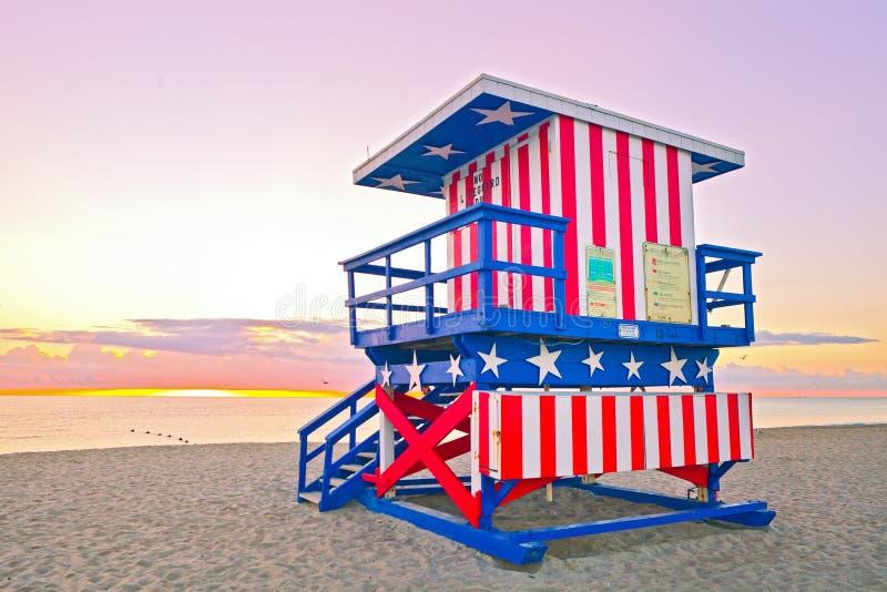Salida del sol en Miami Beach la Florida, con una casa colorida del salvavidas de la bandera americana foto de archivo