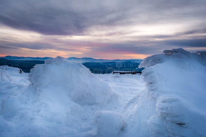 Salida del sol en montañas nevosas foto de archivo