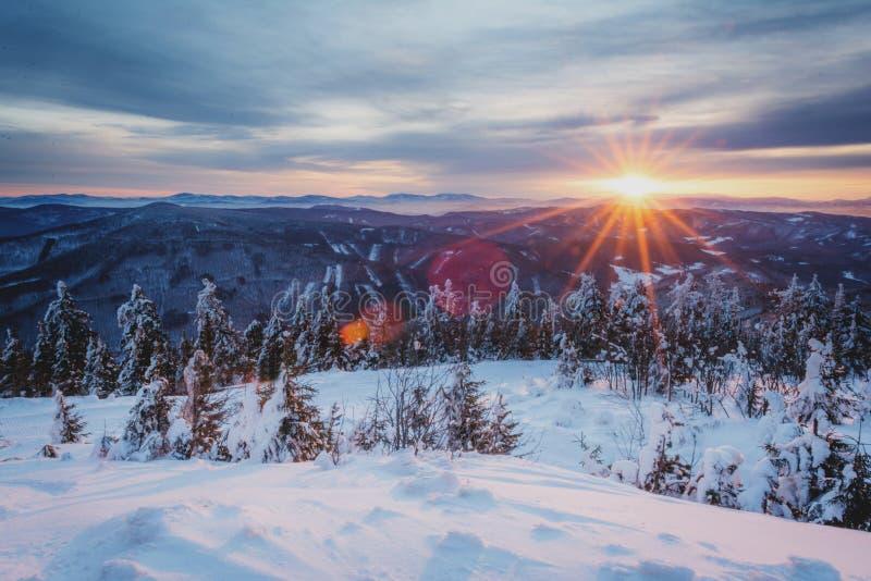 Salida del sol en montañas nevosas imagenes de archivo