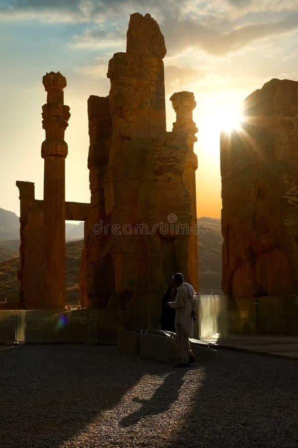 Salida del sol en Persepolis, capital del reino antiguo del Achaemenid Columnas antiguas Sombra de turistas imagen de archivo libre de regalías