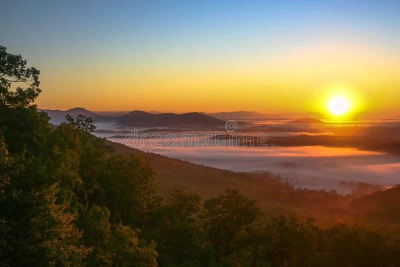 Salida del sol en señuelo del lago con niebla en el valle foto de archivo