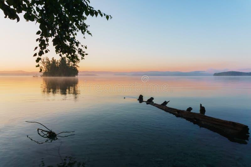 Salida del sol en un lago en las montañas imagen de archivo