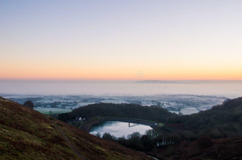 Salida del sol en una mañana escarchada, brumosa de los inviernos Mirada de un depósito a través del campo inglés Colinas de Malv fotos de archivo