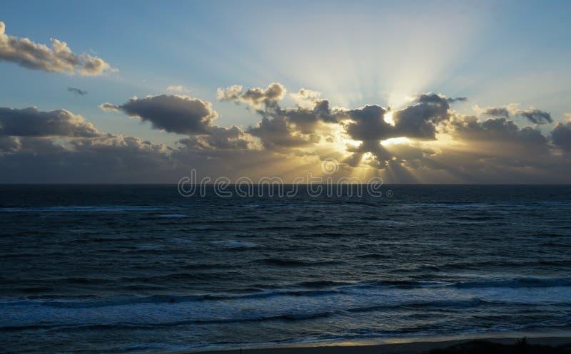 Salida del sol en una playa con los rayos fotografía de archivo