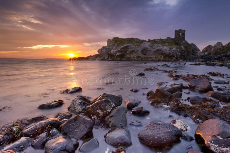 Salida del sol espectacular en el castillo de Kinbane en Irlanda del Norte fotos de archivo
