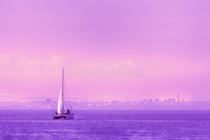 Salida del sol hermosa Barco de navegación con una vela blanca en el mar tranquilo foto de archivo