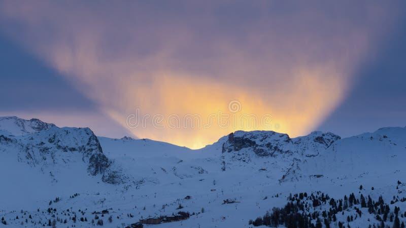 Salida del sol hermosa detrás de las montañas nevosas alpinas en el La francés Plagne de la estación de esquí fotografía de archivo libre de regalías