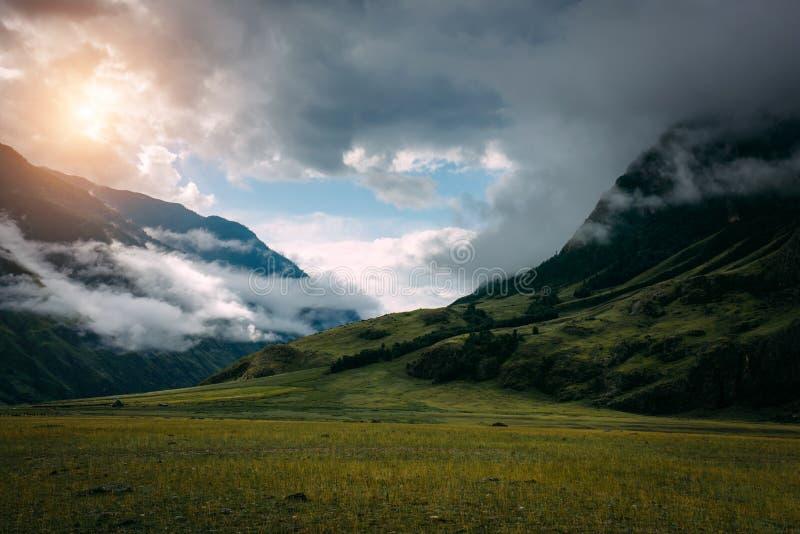 Salida del sol hermosa en monta?as con la niebla blanca abajo Mañana brumosa en montaña, Altai, Rusia Un paisaje de niebla con el foto de archivo