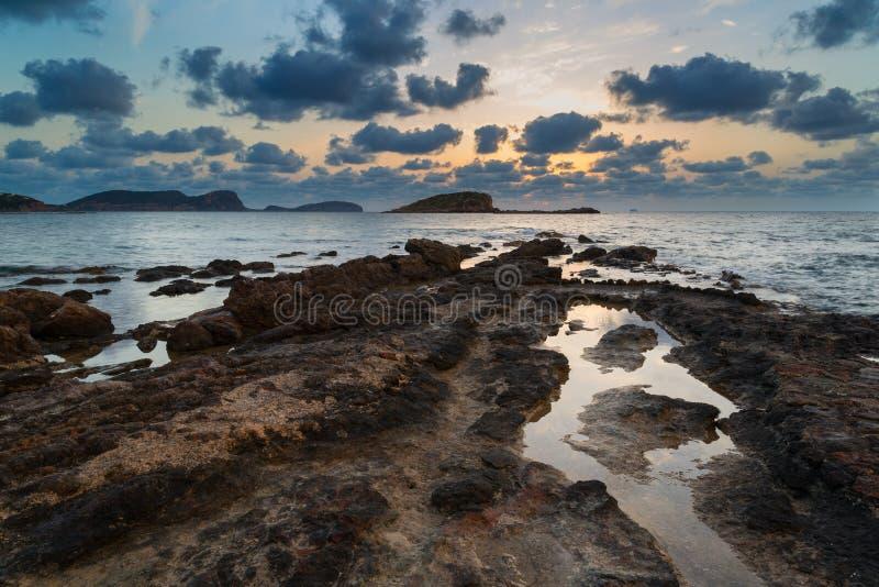 Salida del sol imponente del amanecer del paisaje con la costa costa rocosa y el exp largo imagenes de archivo