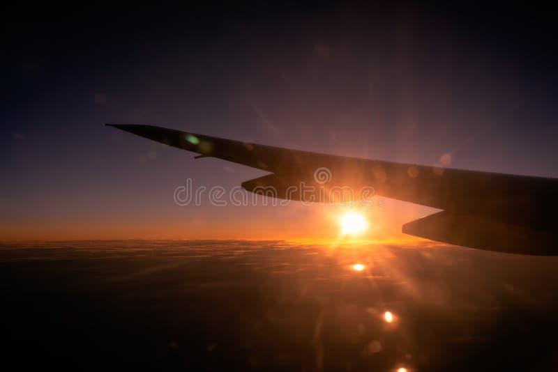 Salida del sol o puesta del sol hermosa sobre las nubes a través de la ventana del aeroplano con el ala fotografía de archivo libre de regalías