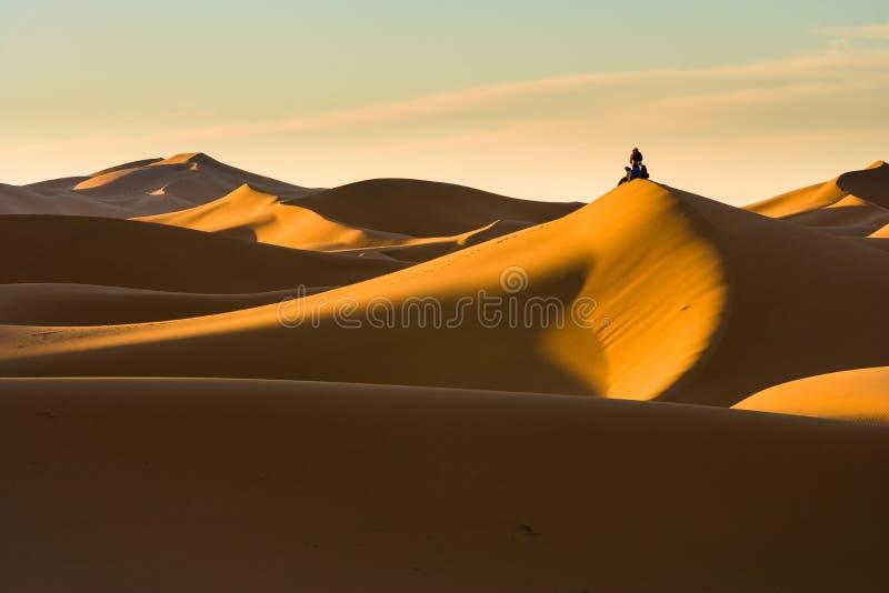 Salida del sol que espera no reconocible de la gente para en Sáhara imagen de archivo