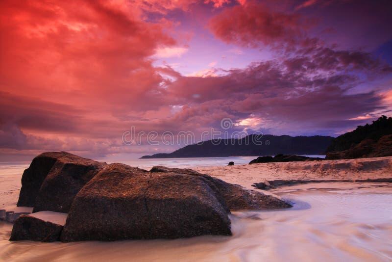 Salida del sol roja del cielo en la playa fotografía de archivo libre de regalías